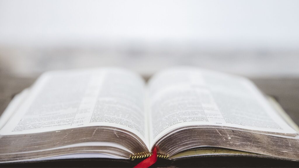 a bible laying open on a table with a blurred background