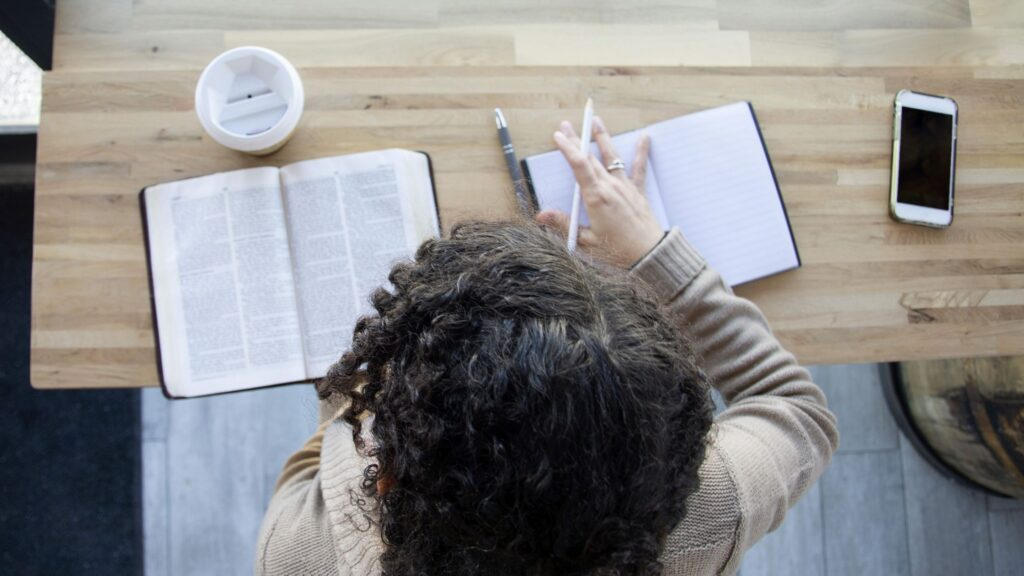 a woman studying her bible with a notebook