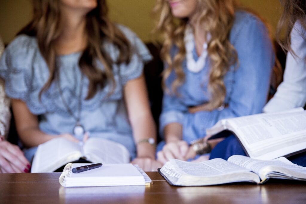 group of women sitting together reading their bibles during bible study group
