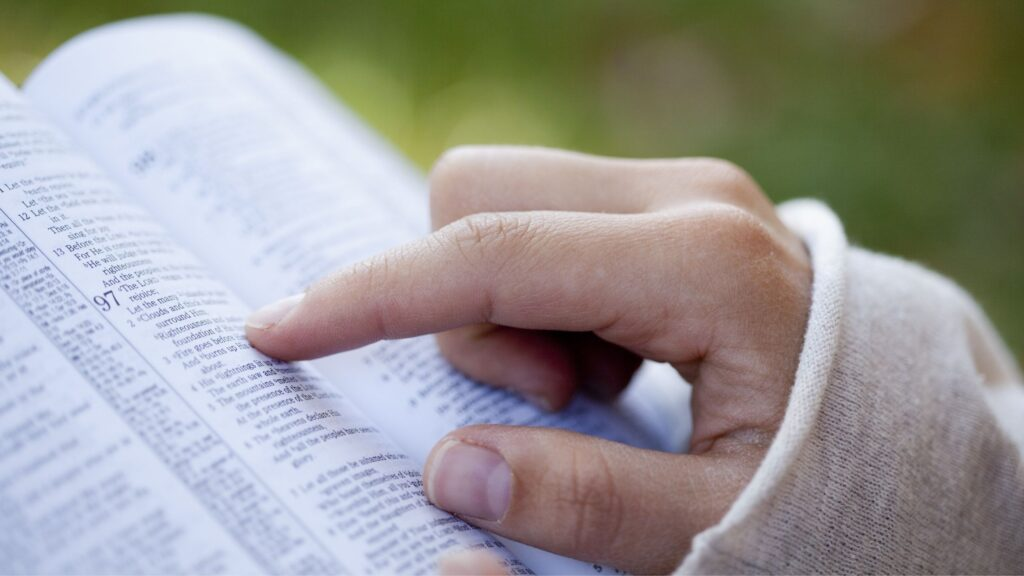 a woman's hand pointing to a verses of Scripture in her bible