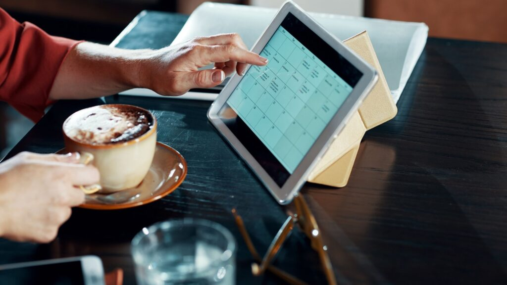 woman drinking coffee and looking at a prayer calendar on her tablet