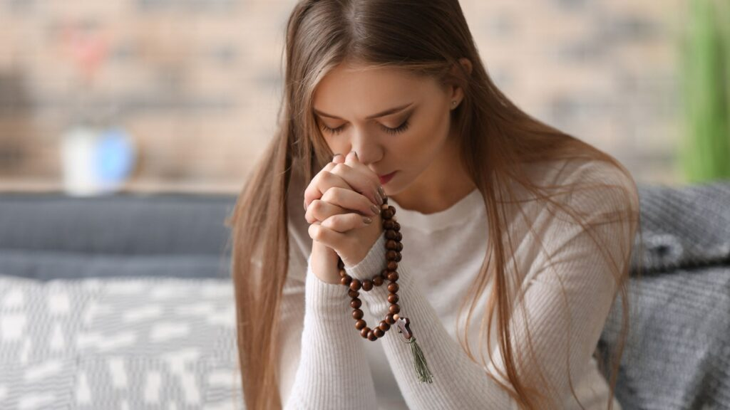 woman sitting on the couch with hands together in prayer