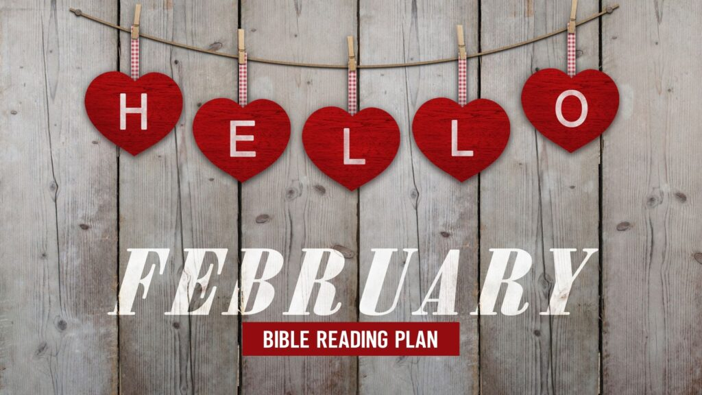 Hello February written with red hearts on a wooden background