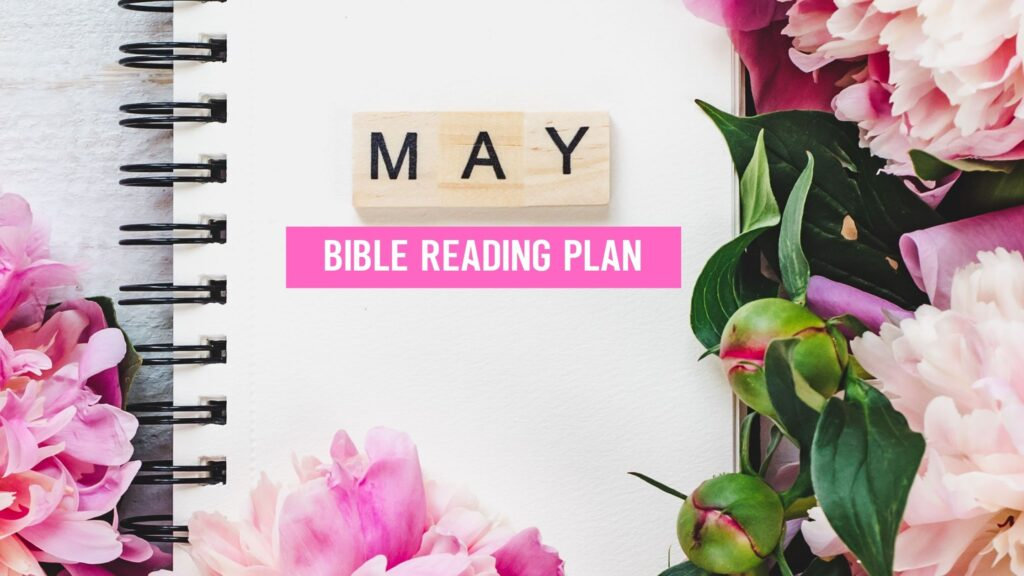 May Bible Reading Plans written on a white notebook surrounded by pink flowers
