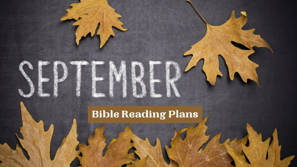 September Bible reading plans written on a chalkboard with yellow fall leaves spread around it