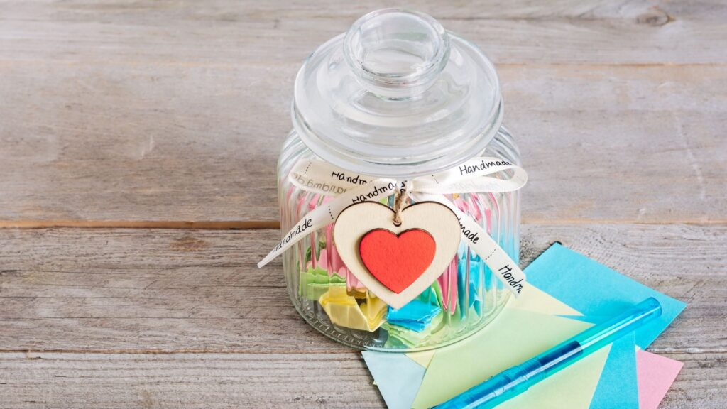 Gratitude Jar sitting on a table filled with gratitude slips