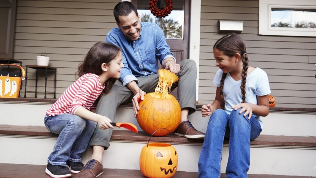 father and daughters carving a pumpkin on the front porch