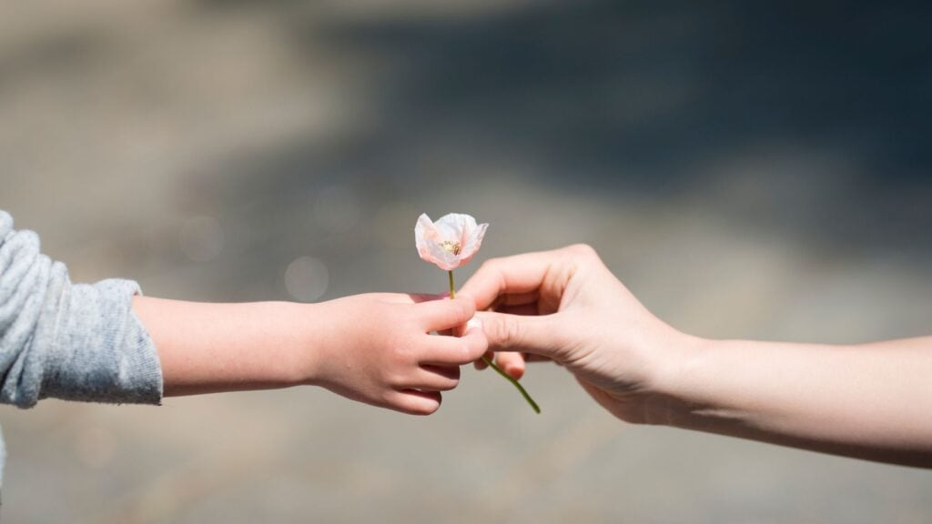 child handing another child a flower